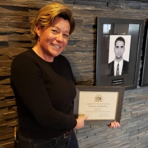 Maryanne poses with her honorary CPVA member certificate next to a photo of John Petropoulos.